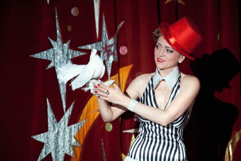 Cyrkowa magik kobieta trzyma biel gołąbki w jej ręce obraz stock