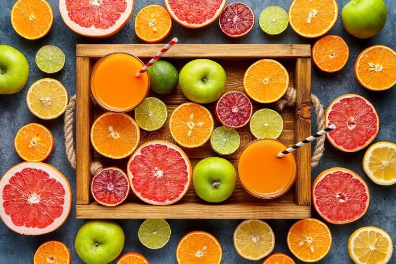 Cytrus owoc żniwa mieszanki pokrajać mieszkanie kłaść w drewnianej tacy na błękita betonu tle, zdrowa jarska żywność organiczna obrazy stock