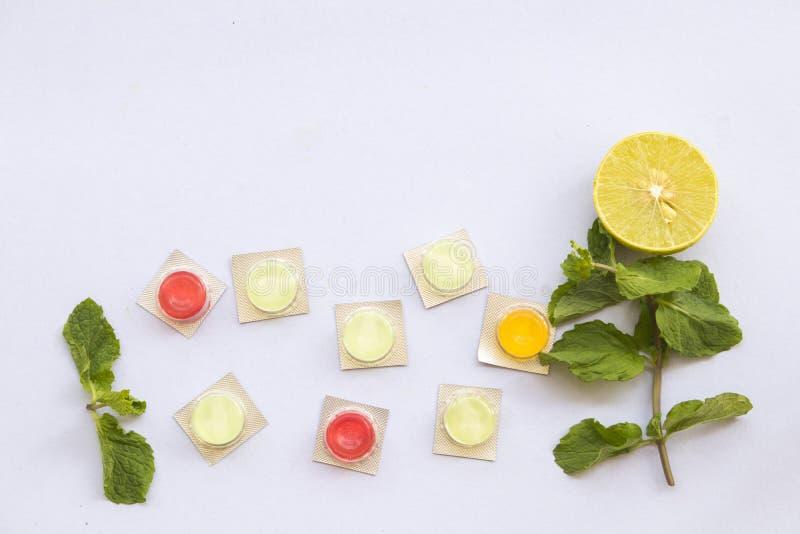 Cytryna, miętowy ziołowy dla kaszlowego bolesnego gardła i kolorowe pigułki, zdjęcia stock