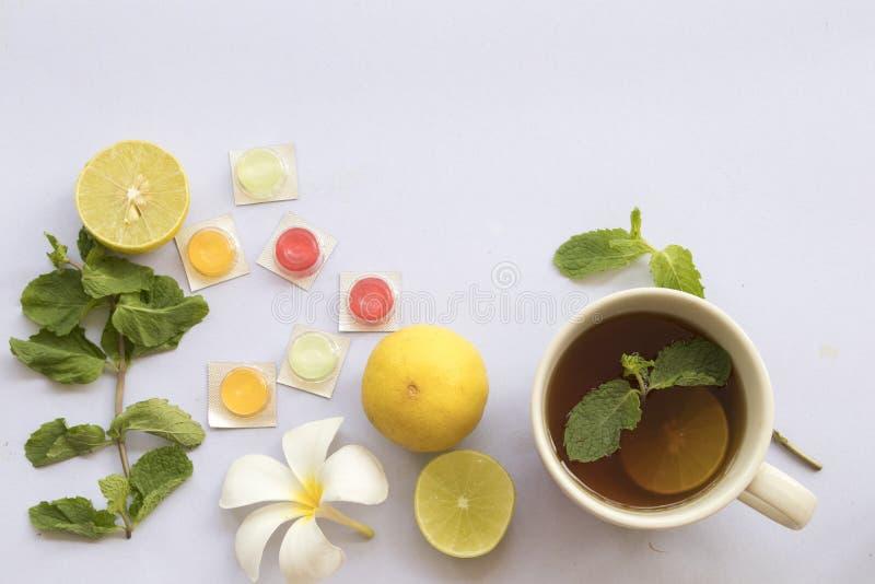 Cytryna, miętowy ziołowy dla kaszlowego bolesnego gardła i kolorowe pigułki, obrazy stock