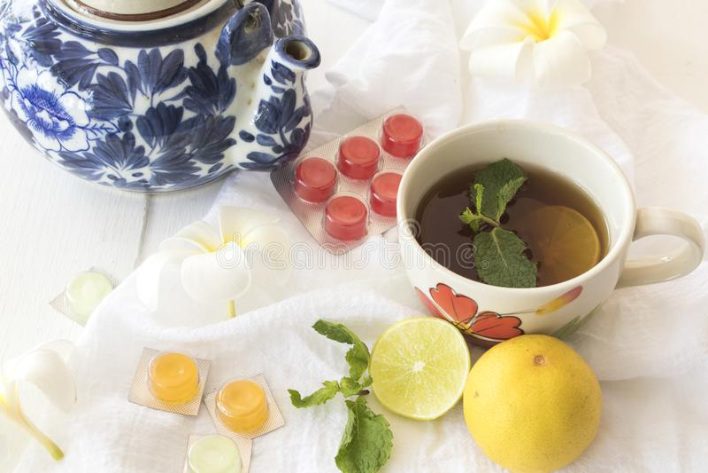 Cytryna, miętowy ziołowy dla kaszlowego bolesnego gardła i kolorowe pigułki, obraz royalty free