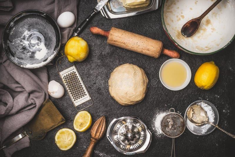 Cytryny ciastko lub torta ciasto z kulinarnymi składnikami i piec narzędzia na ciemnym nieociosanym tle, odgórny widok obrazy stock