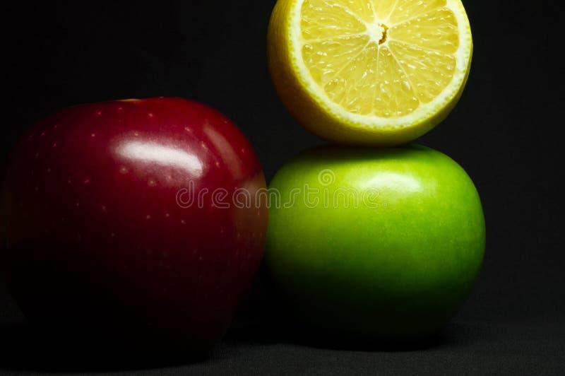 Cytryny, czerwieni i zieleni jabłka na czarnym tle w górę, zdjęcia stock