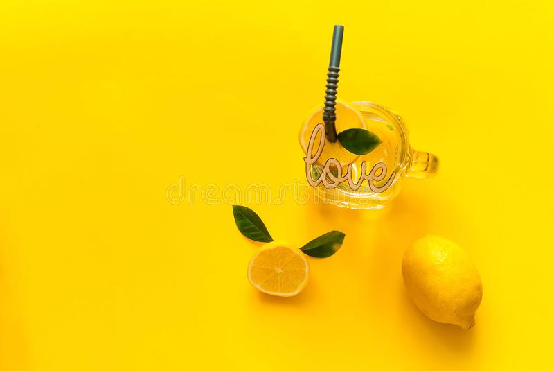Cytryny i cytrus lemoniady napój sodowana woda w szkle z wpisową miłością na żółtym tle zdjęcia royalty free