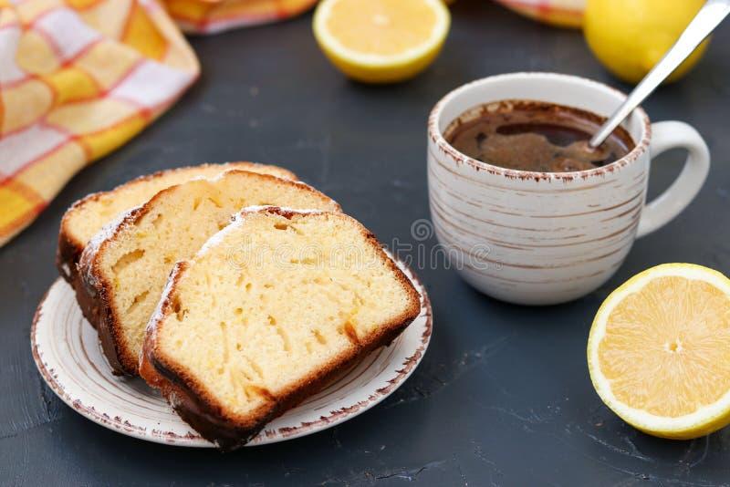 Cytryny słodka bułeczka układał na talerzu przeciw ciemnemu tłu z filiżanka kawy w tle zdjęcia stock