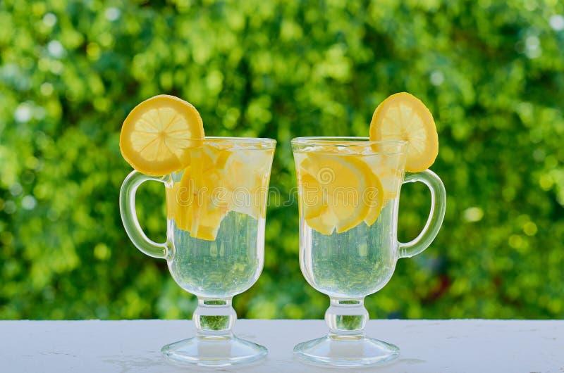Cytryny woda z lodem w szkłach na zamazanym natury tle Zdrowi napoje, lata detox lub diety pojęcie, fotografia royalty free