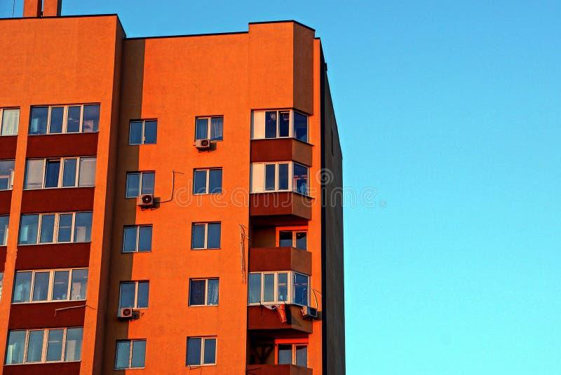 Część brown wieżowiec z balkonami i okno na błękitnym tle zdjęcia royalty free