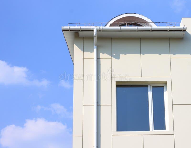 Część budynek ściana z okno i rynną przeciw błękitnemu chmurnemu niebu obraz royalty free