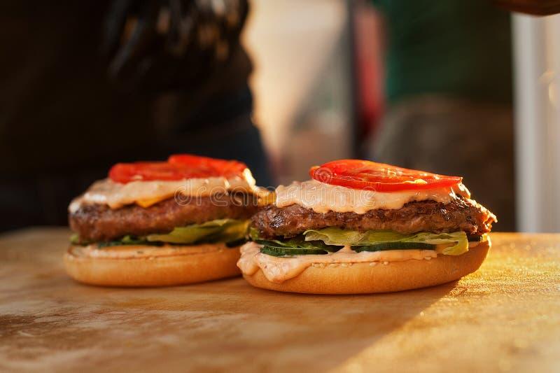 Część hamburger na drewnianej desce Uliczny fast food Zmierzchu światło zdjęcia stock