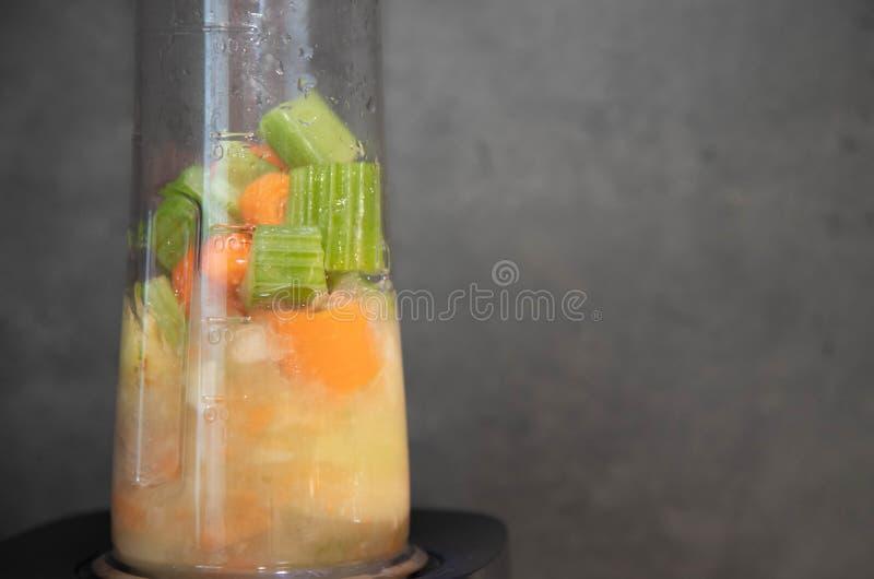 Część kawałki, jabłka i marchewki zmieloni selerowi, Kulinarni smoothies w procesie Przygotowywać smoothie w blender od fotografia royalty free