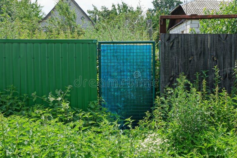 Część stary wiejski ogrodzenie z zamkniętym drzwi przerastającym z zieloną trawą i roślinnością zdjęcie royalty free