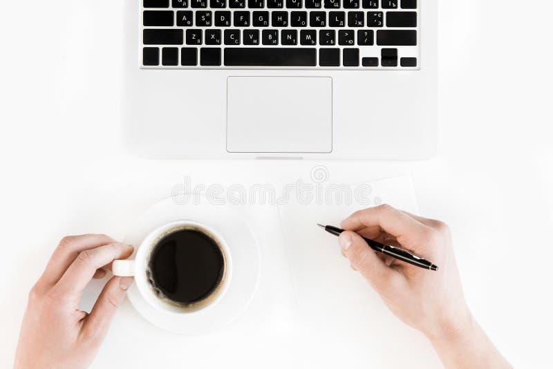 Częściowy odgórny widok trzyma filiżankę kawy i pisze na pustym papierze przy miejscem pracy z laptopem osoba zdjęcia royalty free