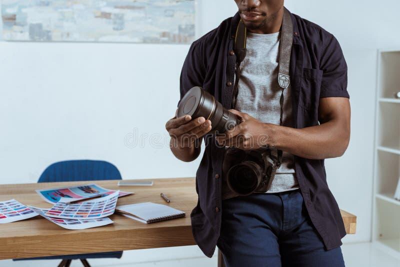 częściowy widok amerykanina afrykańskiego pochodzenia fotograf z fotografii kamerą opiera na miejscu pracy fotografia stock