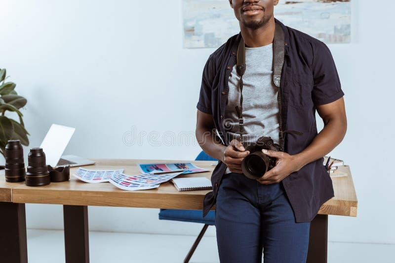 częściowy widok amerykanina afrykańskiego pochodzenia fotograf z fotografii kamerą opiera na miejscu pracy obraz stock