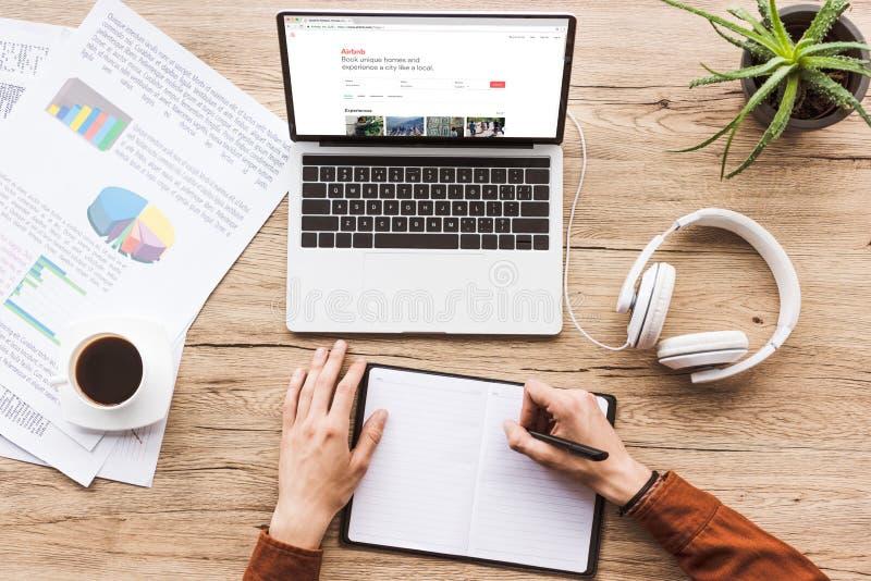 częściowy widok robi notatkom w notatniku przy miejscem pracy z laptopem z airbnb stroną internetową mężczyzna, papiery, filiżank zdjęcia stock