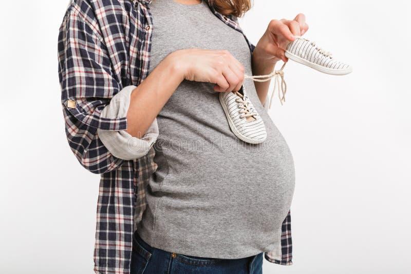 częściowy widok trzyma małych dziecięcych buty kobieta w ciąży obraz stock