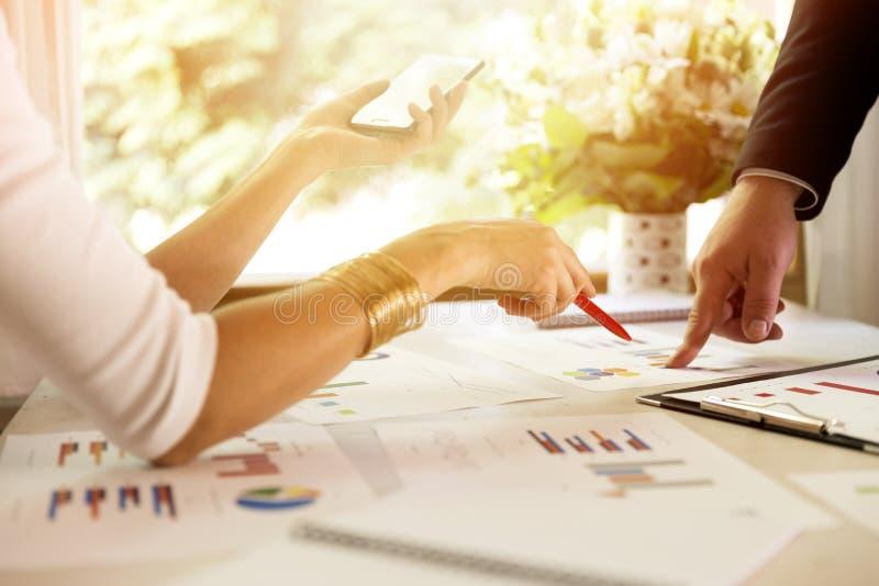Członkowie zaspołu dyskutuje dane przy spotkaniem Wykresy i mapy na stole symbolicznych grup biznesowych sytuacj ludzie obrazy stock