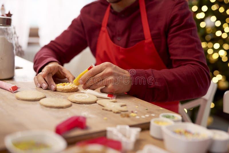 Człowiek dekorujący ciasteczka na Boże Narodzenie zdjęcia stock