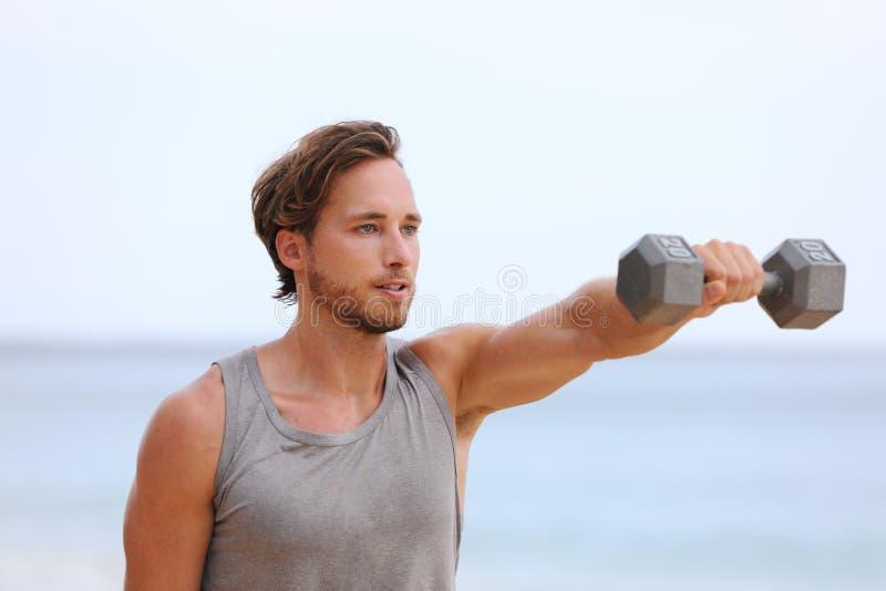 Człowiek od fitness podnoszący dzwonki na plaży wykonujący przedni dzwonek podnosi i e Przemienne przednie podpory — ćwiczenia na zdjęcie stock