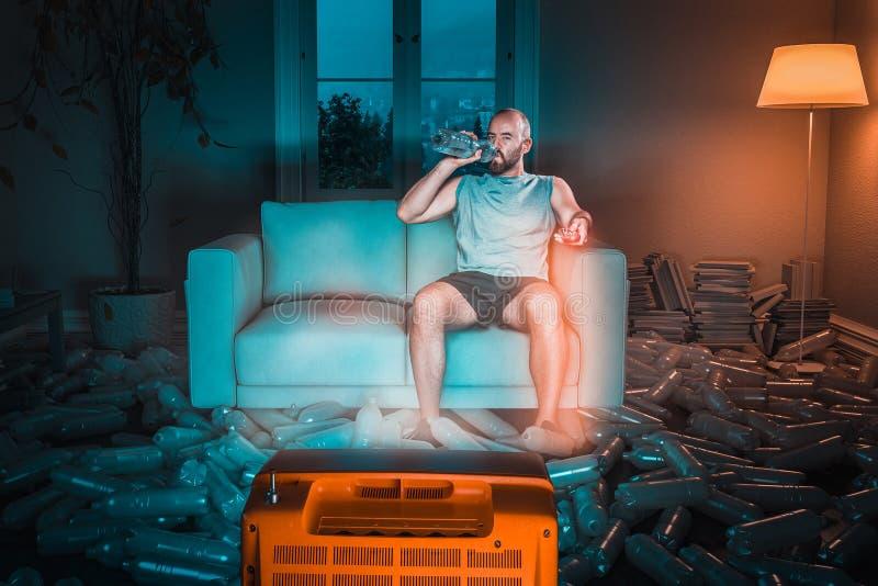 CzÅ'owiek oglÄ…da telewizjÄ™ na kanapie i pije z plastikowej butelki z wodÄ… zdjęcie stock