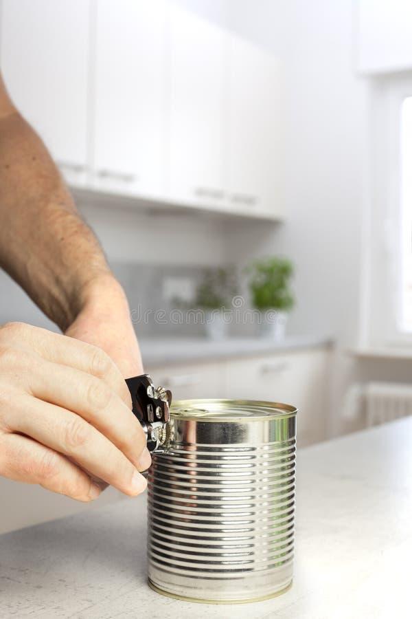 Człowiek otwierający puszkę w białej kuchni obraz royalty free