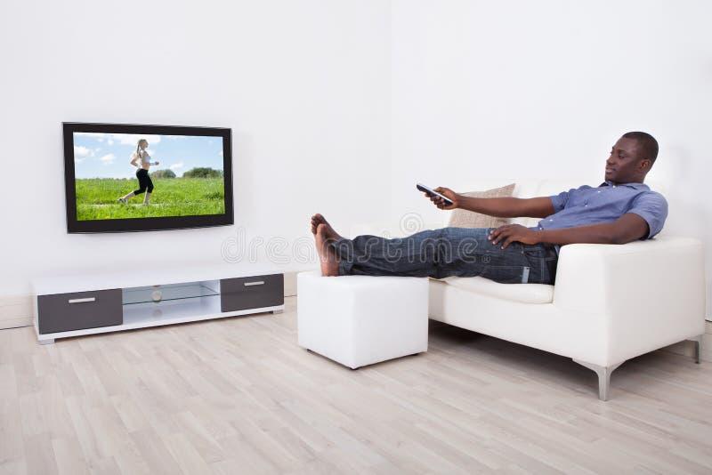 człowiek patrzy telewizyjnych obraz stock