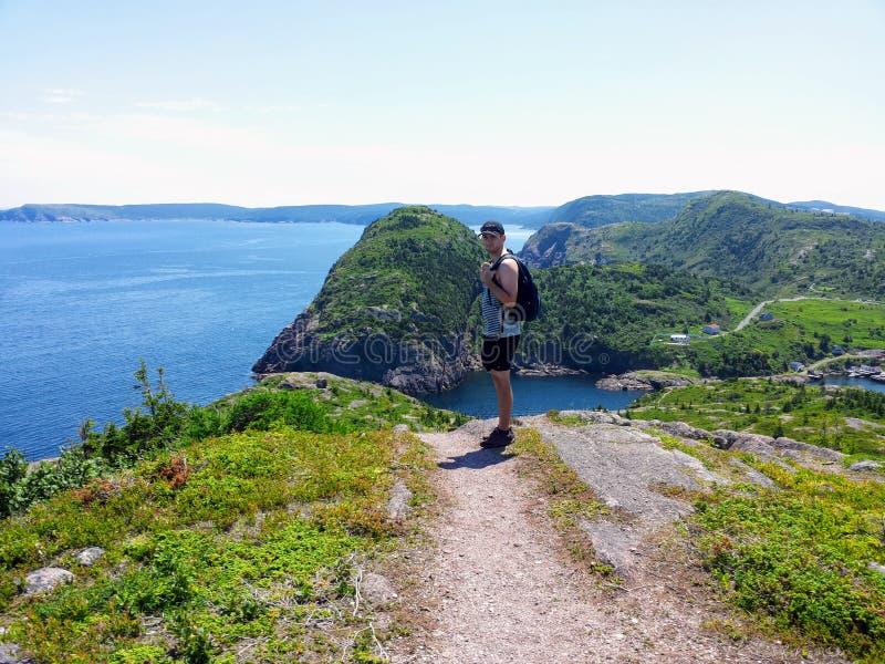 Człowiek postulujący zdjęcie z pięknymi widokami na szlak wzdłuż wybrzeża Nowej Fundlandii i Labradoru, Kanada fotografia royalty free