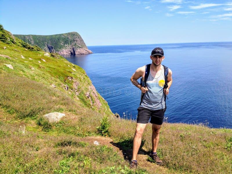 Człowiek postulujący zdjęcie z pięknymi widokami na szlak wzdłuż wybrzeża Nowej Fundlandii i Labradoru, Kanada fotografia stock