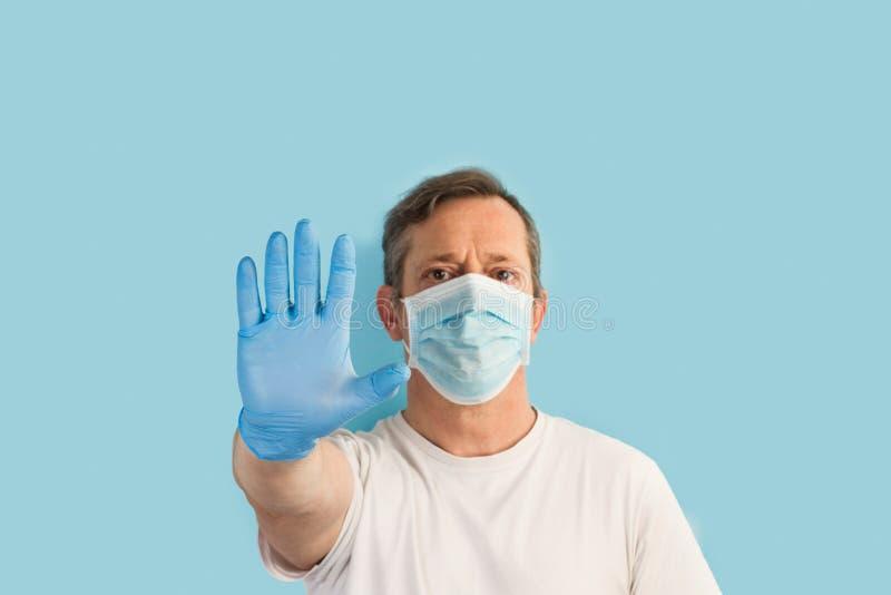 Człowiek stojący na jasnoniebieskim tle z rękawiczkami medycznymi i maską i wykonujący gest zatrzymania obrazy stock