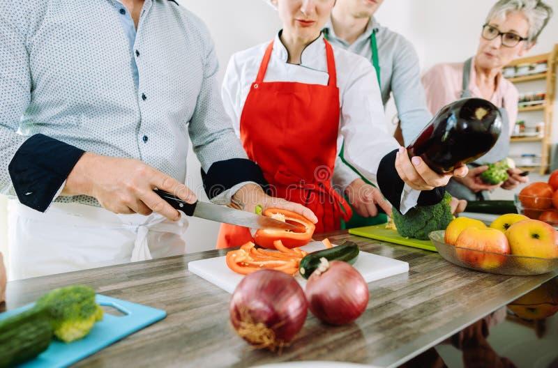 Człowiek szkolący się w kuchni kroić warzywa pod czujnym okiem dietetyka zdjęcie royalty free
