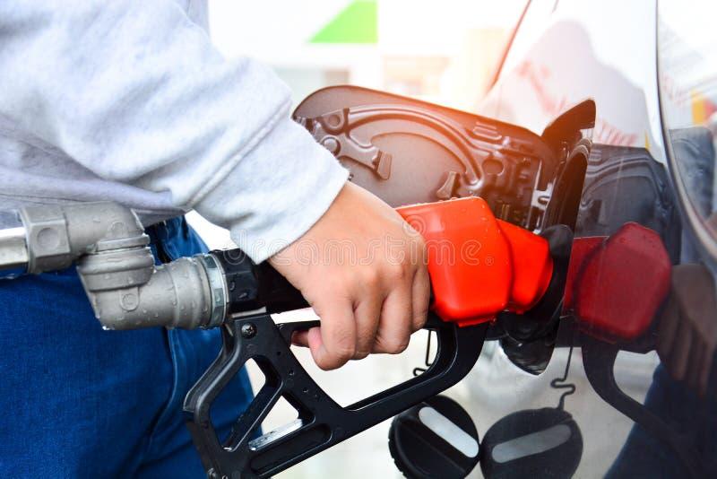 Człowiek trzymający dyszę z czerwonym paliwem i pompujący paliwo do benzyny w samochodzie na stacji gazowej, paliwach samochodowy obraz royalty free