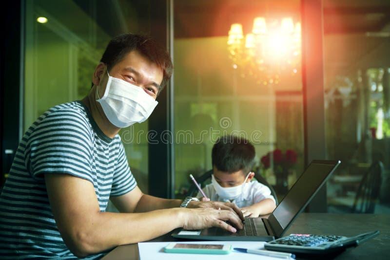 Człowiek z azji kwarantanny i dzieci noszące maskę ochronną pracujące na komputerze w domu, podczas gdy wirus covid-19 jest atako obrazy royalty free