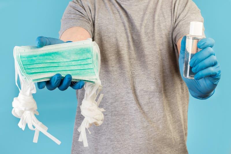 Człowiek z niebieskimi rękawiczkami medycznymi trzymający alkohol żelowy i maski medyczne zdjęcia royalty free