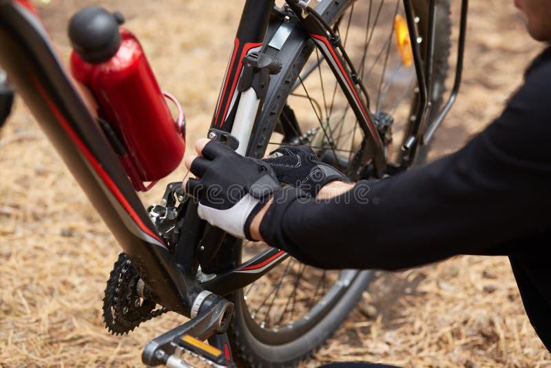 Człowiek zatrzymuje się, jest na zewnątrz, naprawia rower własnymi siłami, zmienia szczegóły, problemy z ruchem, czerwona butelka zdjęcie royalty free
