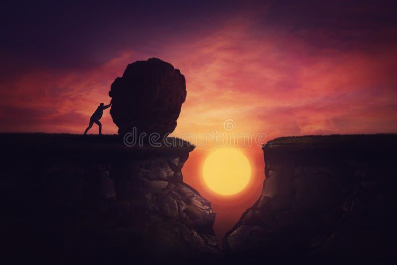 Człowiek znalazł rozwiązanie w trudnej sytuacji, popychając olbrzymi głaz, by wypełnić przeszkodę. Używając skały, przykryj otwór fotografia stock