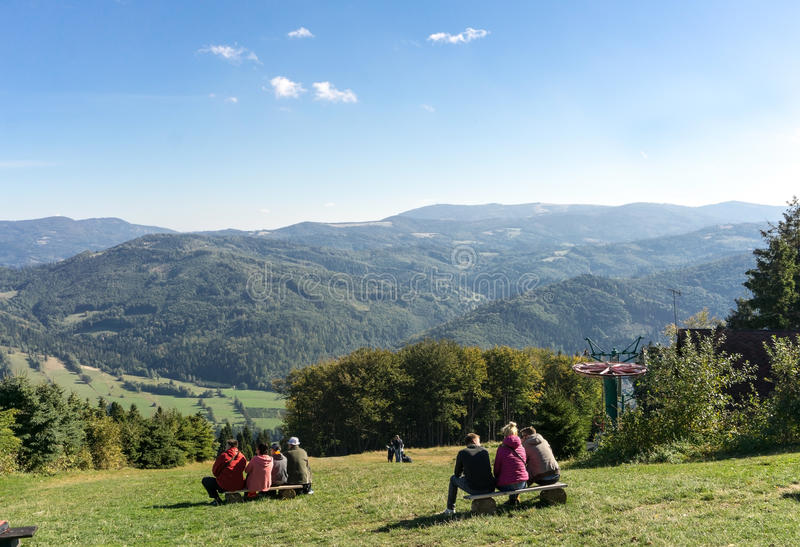 CZANTORIA MOUNTAIN, SILESIAN BESKIDS, POLAND, OCTOBER 03, 2015. People are resting on a bench in the mountains on a sunny autumn day - beautiful mountain stock images