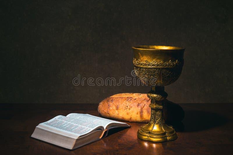 Czara z wino chlebem i Świętą biblią na stole zdjęcia royalty free