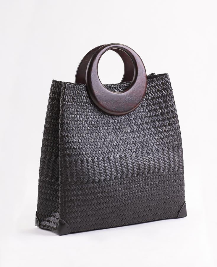 Czarna łozinowa torebka z drewnianymi rękojeściami odizolowywać zdjęcia stock