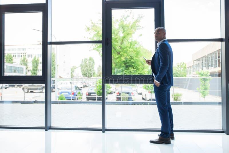 Czarna Amerykańska biznesmen pozycja przy okno, Dzwoni Someone Przez telefonu komórkowego zdjęcie royalty free
