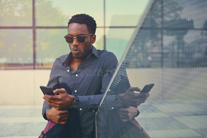 Czarna Amerykańska samiec używa mądrze telefon obraz royalty free