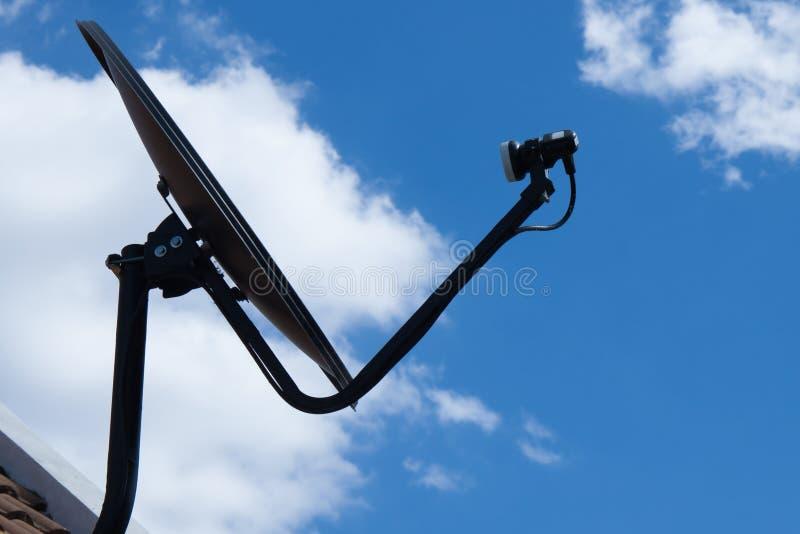 Czarna antena satelitarna z niebieskim niebem i biel chmurą zdjęcie royalty free