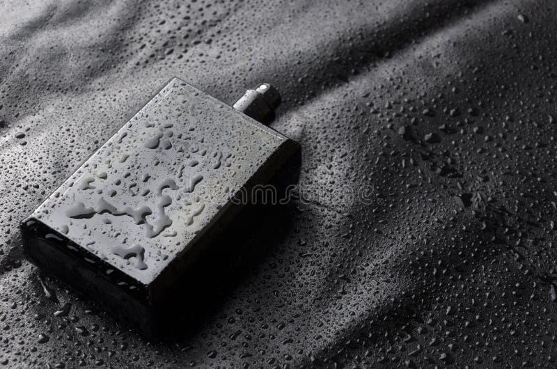 Czarna butelka parfume z otwartą nakrętką na czerni wodzie opuszcza tło Closeu strzał obrazy royalty free