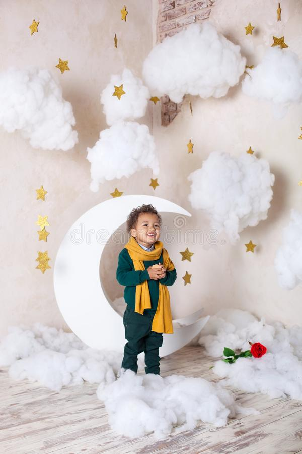 Czarna chłopiec zamknięta w górę portreta Portret rozochocona uśmiechnięta chłopiec w żółtym szaliku Dzieci?stwo Mała czarna chło fotografia stock