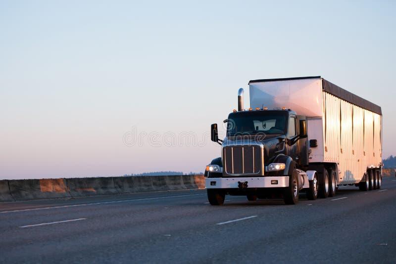 Czarna ciężka klasowa duża takielunku semi ciężarówka z dzień taksówką dla lokalnych delikatesów obraz royalty free