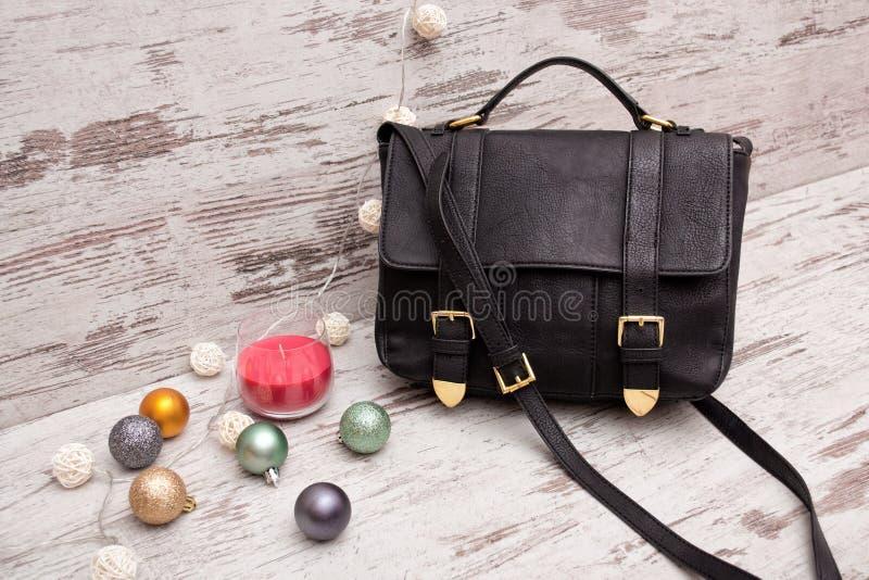 Czarna damy torebka na drewnianym tle, Bożenarodzeniowych ornamentach, girlandzie i świeczce, obrazy royalty free