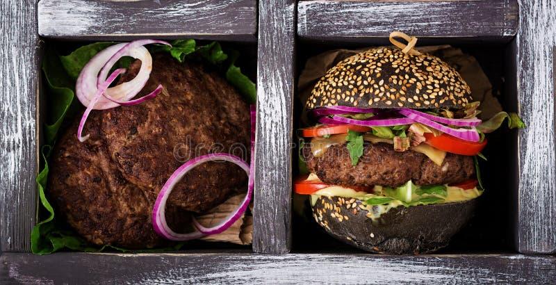 Czarna duża kanapka - czarny hamburger z soczystym wołowina hamburgerem, serem, pomidorem i czerwoną cebulą w pudełku, obrazy royalty free