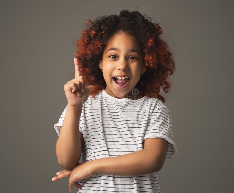 Czarna dzieciak dziewczyna pomysł, robi palcowi w górę gesta zdjęcie royalty free