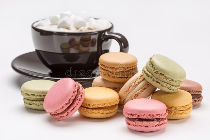 Czarna filiżanka kawy z białymi marshmallows, kolorowi Francuscy macaroons fotografia royalty free