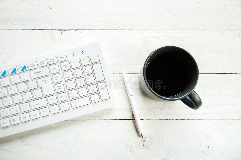 Czarna filiżanka z kawową i komputerową klawiaturą na białym stole bia?y t?a drewniane zdjęcia stock
