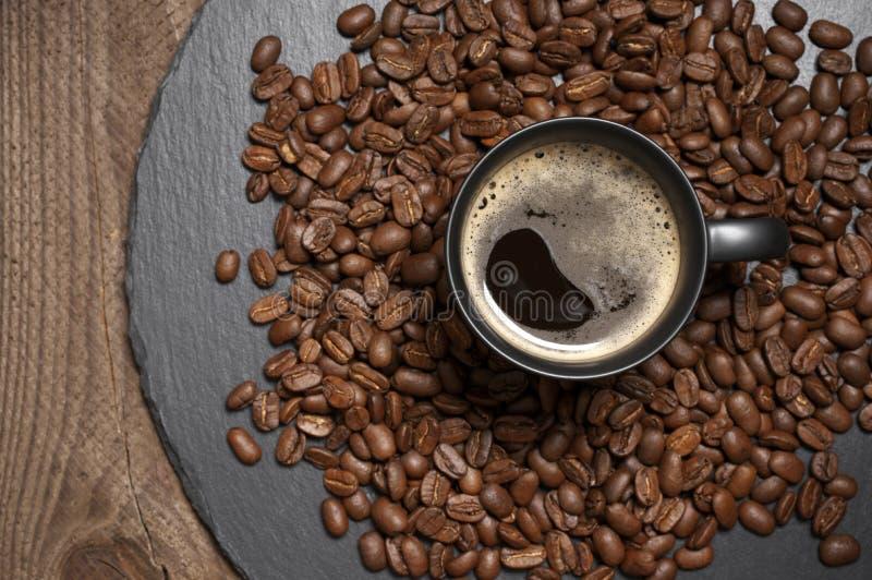 Czarna fili?anka gor?ca kawa w kawowych fasolach obraz stock